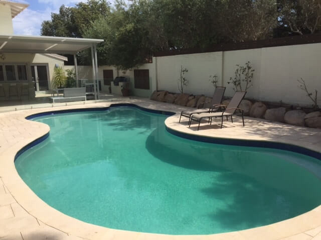 Traditional style curved pool with Beach Champagne pavers & bullnose