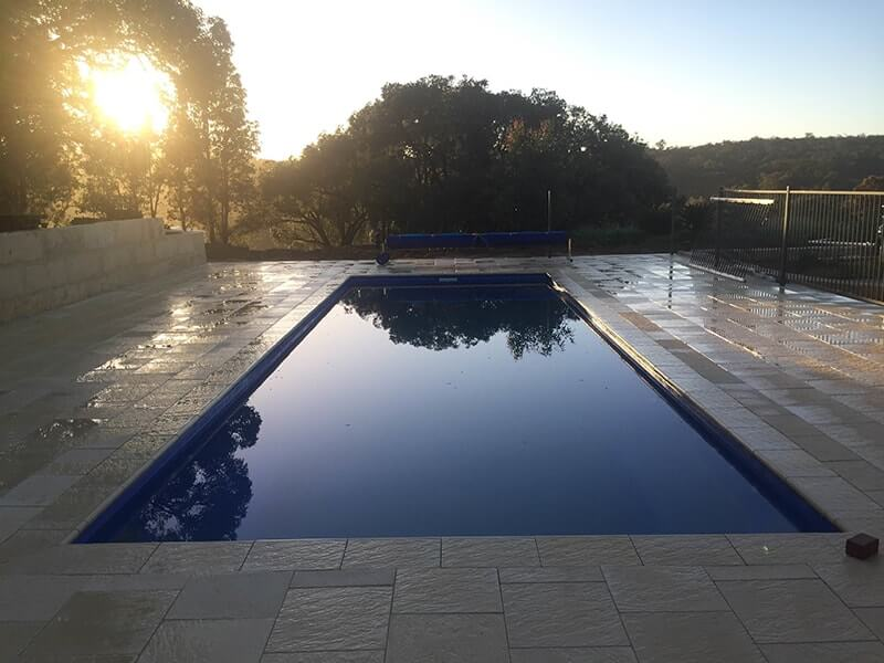 Castlestone capping & paving surrounding pool in Perth hills at sunrise