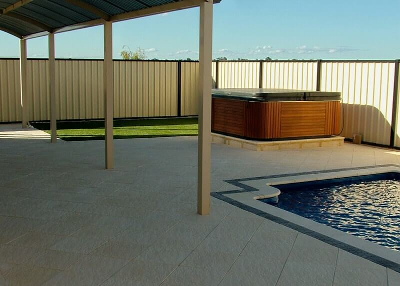 Pool area and spa on raised platform in Castlestone Beach pattern paving and capping
