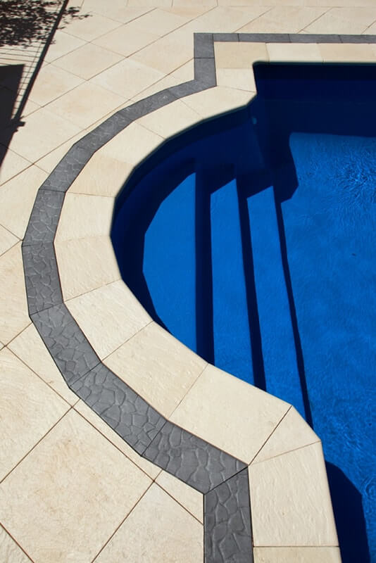 Roman style pool with Castlestone bullnose capping and Pebble border