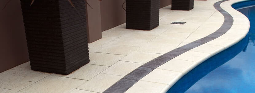 Castlestone around a curved pool with bullnose capping, pebble border in charcoal
